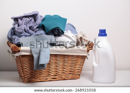 Dirty clothes in the laundry basket and a bottle of detergent - stock photo