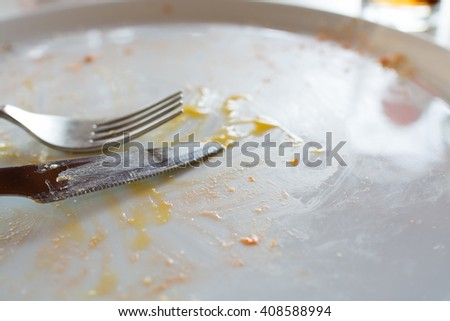 Dirty dish, empty plate with fork and knife - stock photo