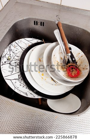 Dirty dishes in kitchen sink - stock photo
