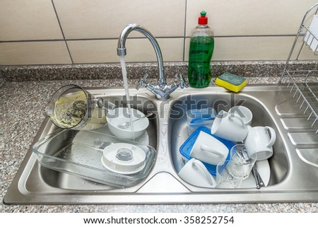 Dirty dishes in the sink, water is running, everything is ready for washing. - stock photo