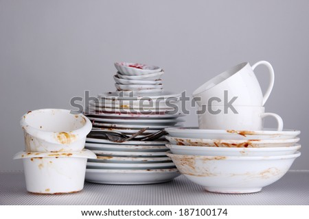 Dirty dishes on gray background - stock photo