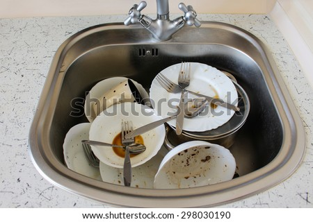 Dirty dishes: plates, cup, forks, spoons in the sink - stock photo