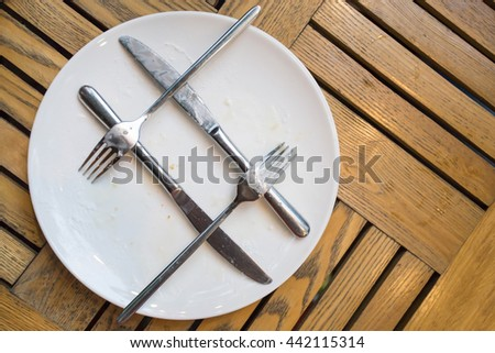 dirty dishes with forks and knives and two glasses - stock photo