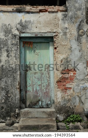 Dirty Door. Old wooden door on a derelict house. This house is in need of repair or renovation. A symbol of urban decay. - stock photo