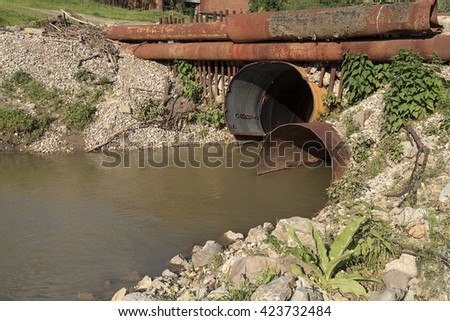 Dirty drain polluting a river - stock photo