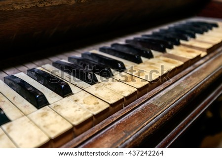 Dirty dusty antique piano in shed. Shallow DOF - stock photo