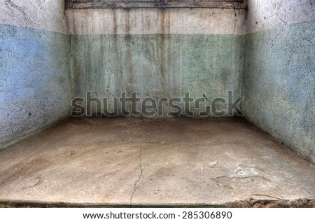 Dirty, empty enclosed space in a derelict building. Ideal as a backdrop for your dark and gloomy subject. - stock photo