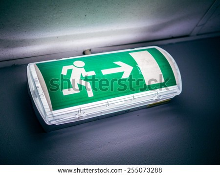 Dirty exit sign glowing in a dark room - stock photo