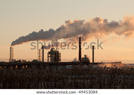 Dirty factory smoke rising at sunset, view from the lake