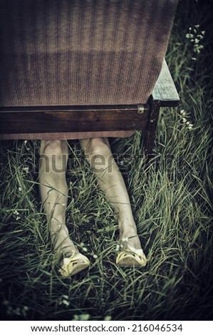 Dirty female legs sticking out from under an armchair in a field, dark mood unusual concept - stock photo