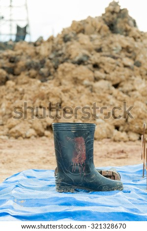 Dirty galoshes (rubber boots) at a construction site.Selective focus. Very shallow Depth of Field, for soft background. - stock photo