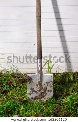 dirty garden spade stuck in the ground on a white wooden background - stock photo