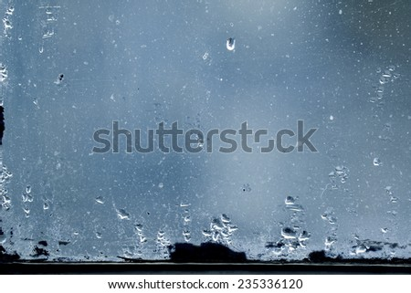 dirty glass with water vapor condensation drops, cold blue abtra - stock photo