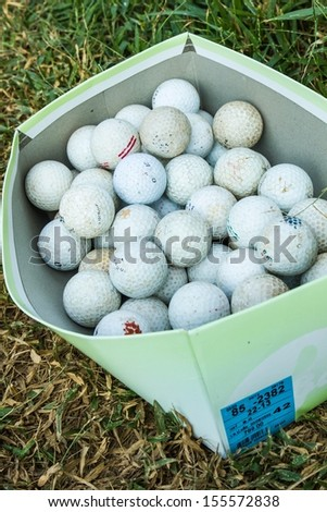 Dirty golf balls in cardboard boxes on the grass. - stock photo