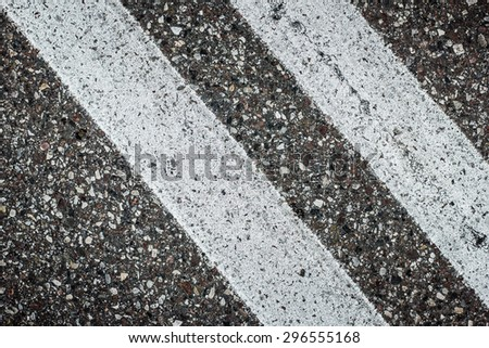 Dirty grunge white lines on asphalt. - stock photo