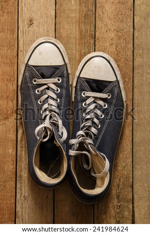 Dirty gumshoes on wooden background - stock photo