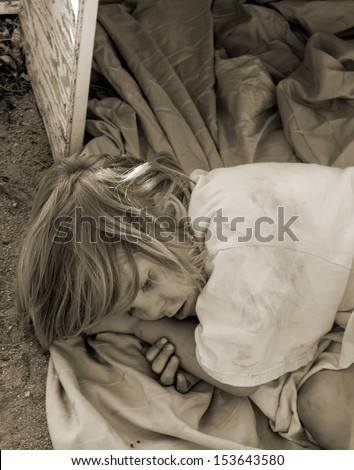dirty homeless child laying down in an old box - stock photo