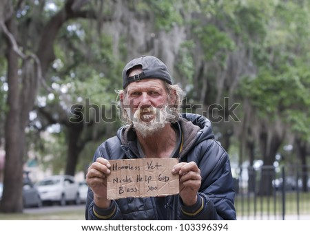 Dirty homeless man holding sign asking for help - stock photo