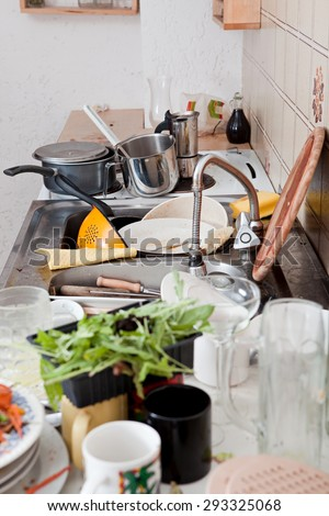 dirty kitchen with messy crockery, leftovers and filthy kitchenware - stock photo