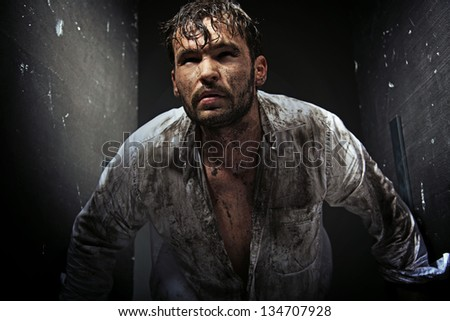 Dirty man between grunge walls - stock photo