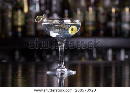 Dirty martini cocktail on bar counter - stock photo