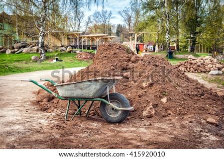 Dirty metal garden wheelbarrow on the bare ground - stock photo
