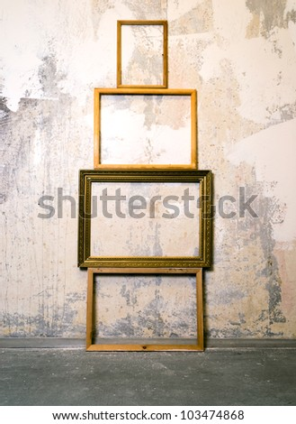 Dirty old room with empty picture frames on the wall. Grunge vintage interior - stock photo
