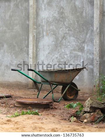 dirty old wheelbarrow standing near the wall