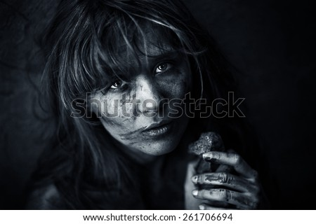Dirty orphan with a piece of bread - stock photo