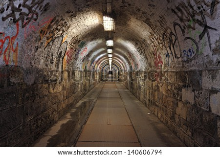 Dirty pedestrian tunnel at night - stock photo