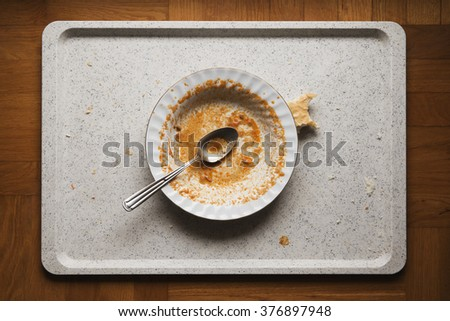 dirty plate after a finished meal stained with food leftovers on a tray - stock photo