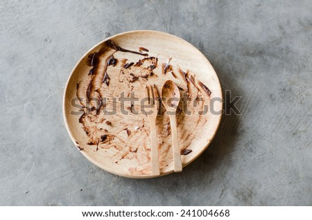 Dirty Plate, Spoon and Fork on cement background. Top View Text Space - stock photo