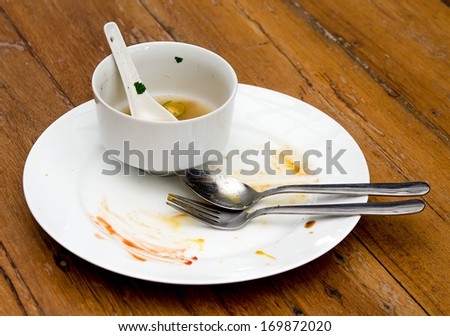 Dirty plate with spoon  and fork on wood table - stock photo