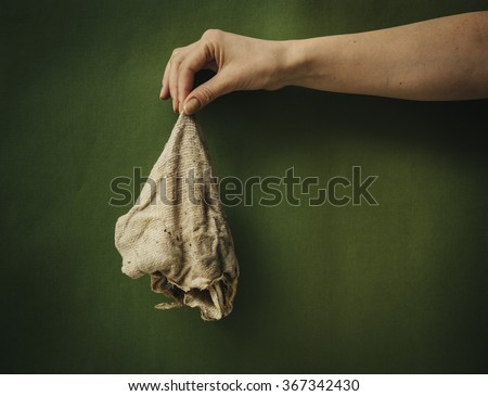 Dirty rags in a female hand. - stock photo