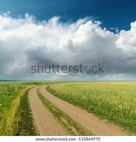 dirty road in fields and low clouds on horizon - stock photo