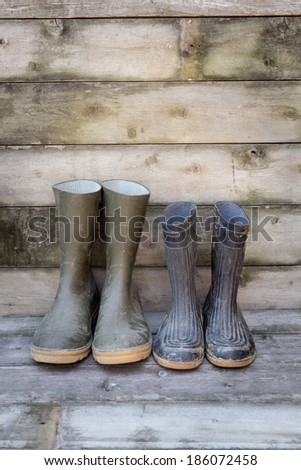 Dirty rubber boots on wooden floorboard  - stock photo