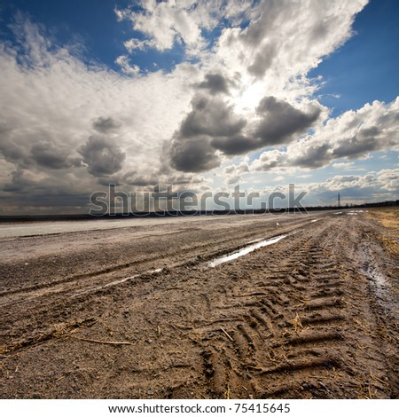 Dirty rural road and cloudy blue sky