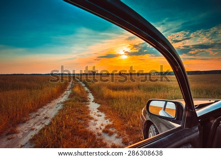 Dirty rural road in autumn fall field, meadow, countryside. View from car window. Freedom and dream concept dramatic sky - stock photo