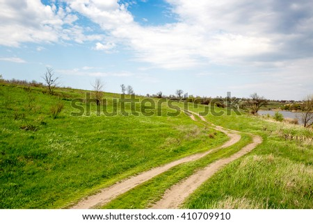 dirty rut road across green slope under cloudy sky - stock photo