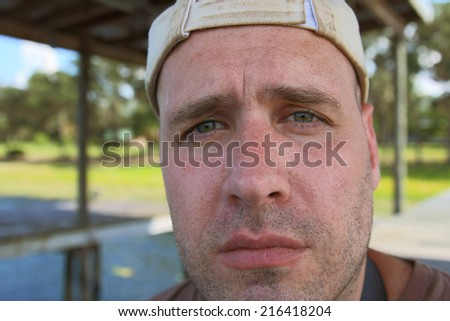 Dirty scruffy unshaven burly masculine man wearing dirty hat outside looking depressed disappointed disbelieving disgusted emotional incredulous sad uncertain unhappy worried confused concerned - stock photo