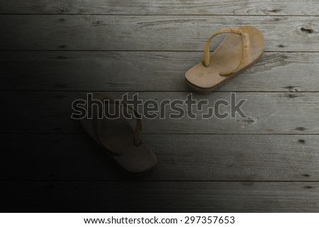 dirty slippers on old wood with dark and lighting