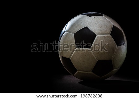 Dirty soccer ball on black background