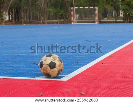 Dirty soccer ball on soccer field - stock photo
