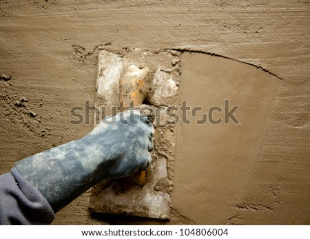 dirty trowel with glove hand plastering cement mortar in the wall - stock photo