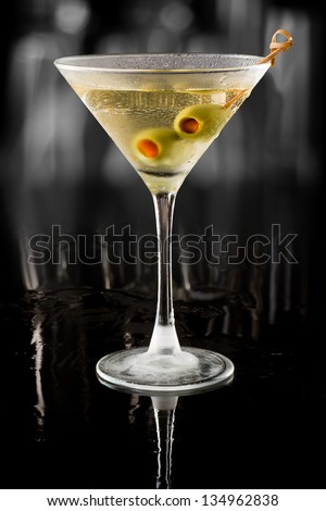 dirty vodka martini served on a dark bar garnished with large green olives - stock photo