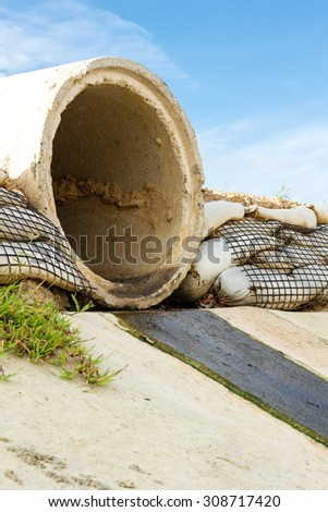 Dirty water stems from the pipe polluting the river - stock photo