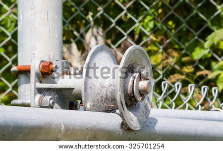 Dirty worn metal roller on frame of chain-link fence gate with rusted screw and nut. - stock photo