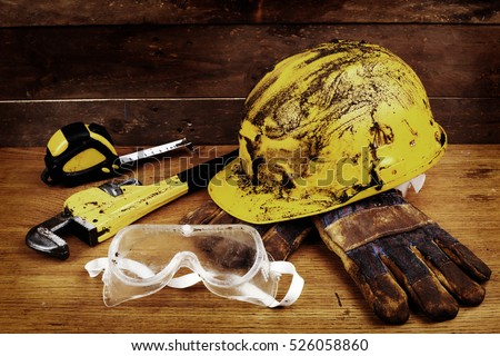Dirty yellow helmet and tools on work place