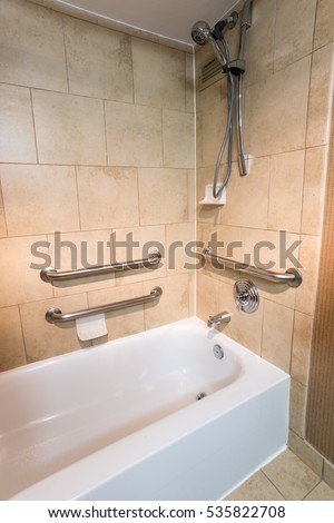 disability access bathtub shower in a hotel room with grab bar hand rails