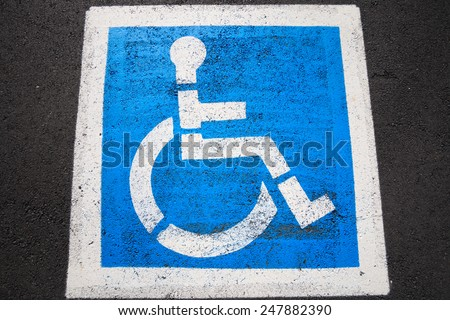 Disability sign on the road background - stock photo